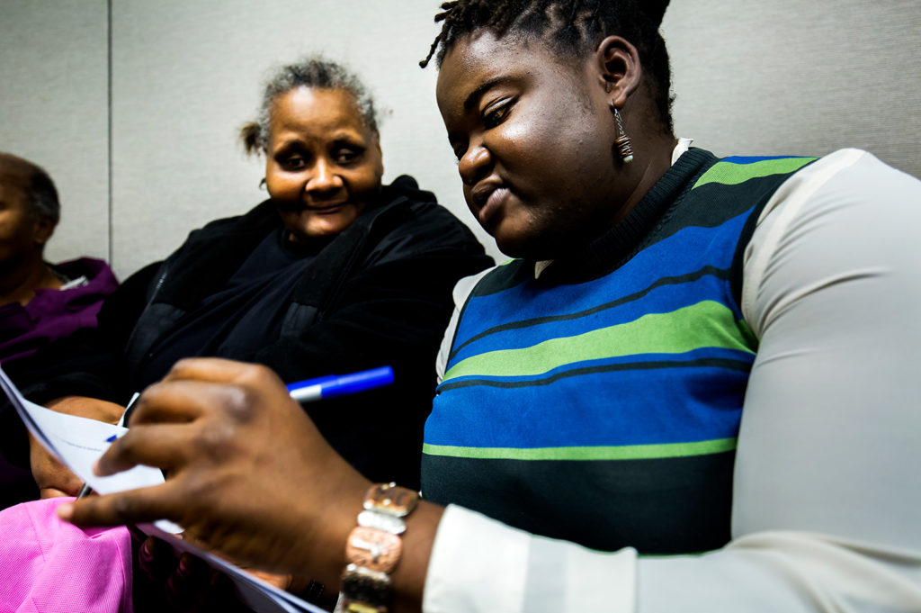 Assistant Professor Tierra Bills confers with a Benton Harbor resident at a workshop.