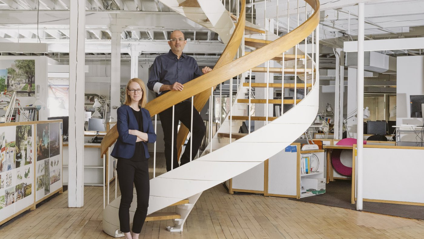 Portrait of Caitlyn Clauson and Romil Sheth by a staircase in their office