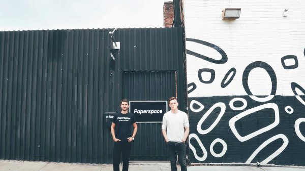 Dillon Erb and Daniel Kobran standing in front of a black-and-white mural