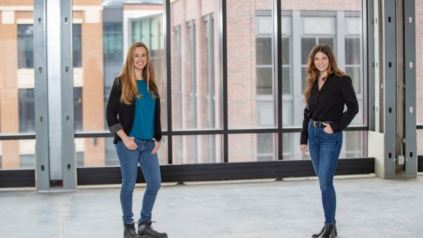 Portrait of Meredith McLellan and Angela Fortino next to a window overlooking the city